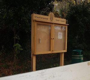 A wooden village noticeboard
